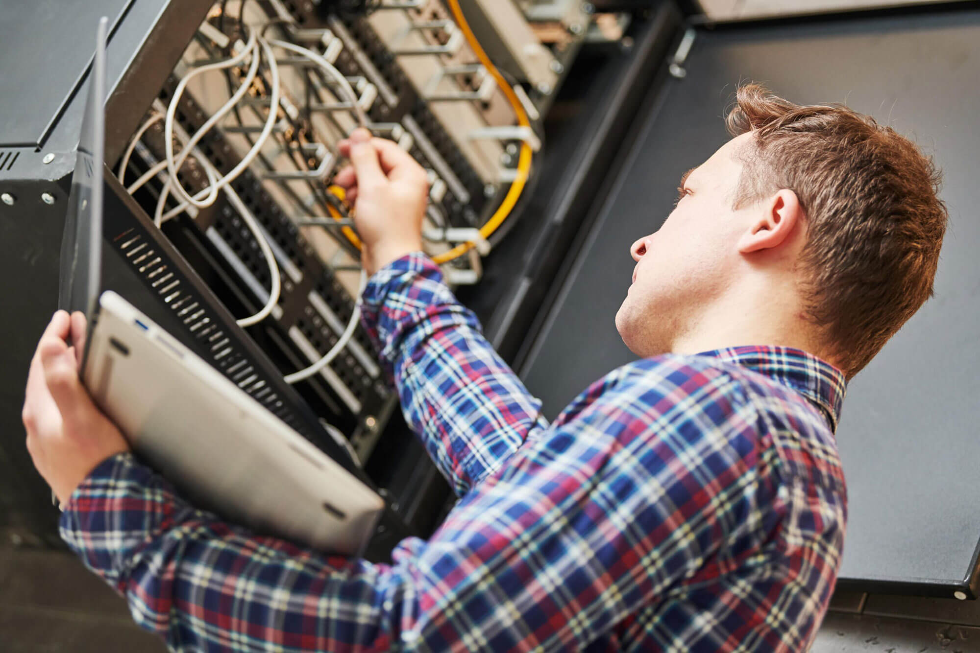 man plugging cables into server rack